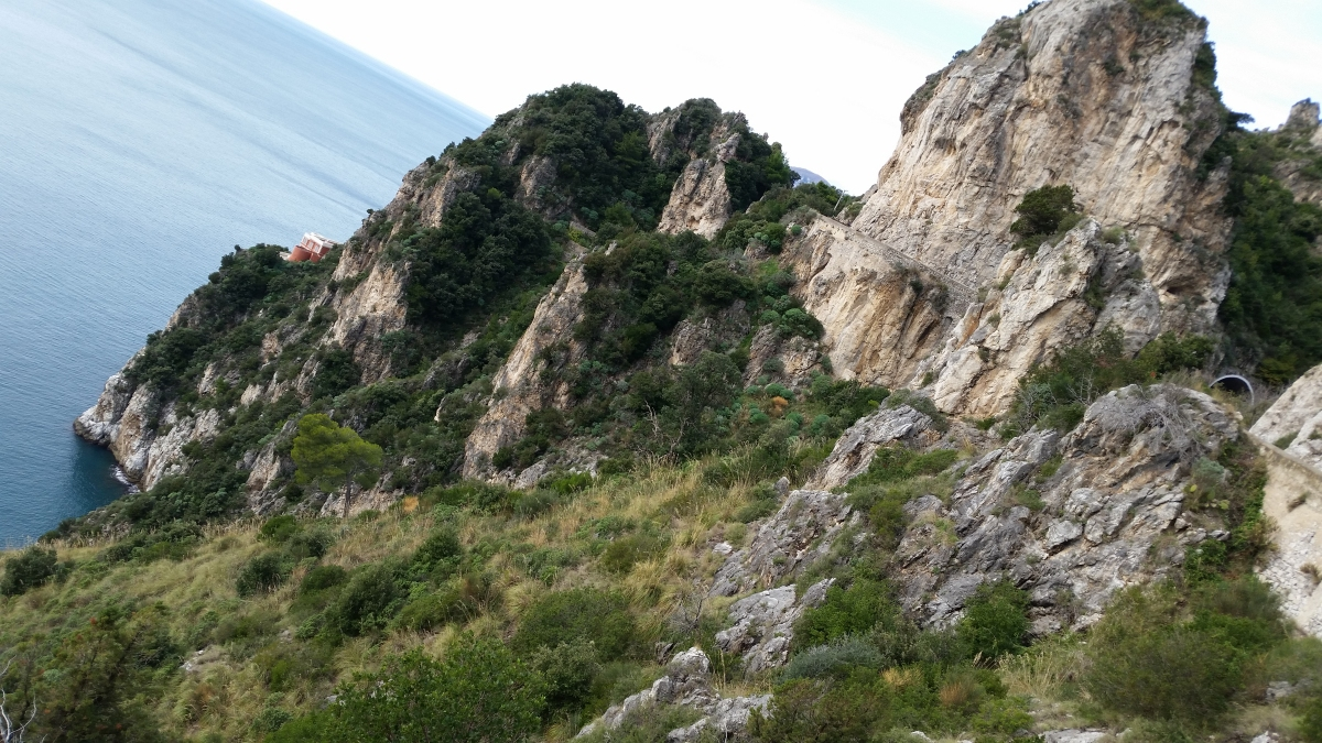 Cliffs plunge steeply into the azure sea at Capo d'Orso near Erchie